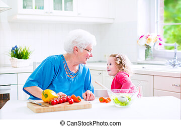 Grandmother and little girl making salad - Beautiful senior...