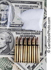 Powder Bag - Bullets on dollar banknotes with bag of white...