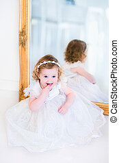 Little girl in a white dress next to a mirror - Sweet curly...