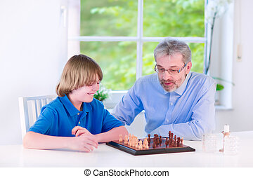 Happy grandfather playing chess with his grandson