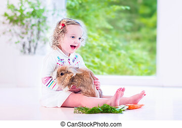 Little girl playing with a bunny - Adorable toddler girl...