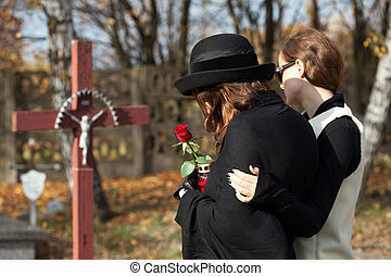 Women on the cemetery - Woman supporting friend in mourning...