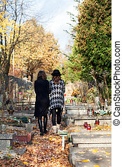Sisters in mourning walking at the cemetery after mother...
