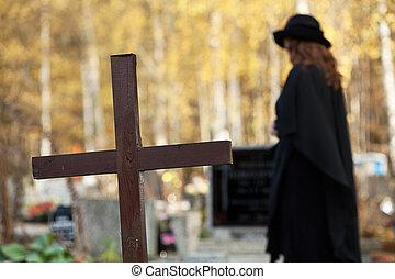 Widow suffering - Widow standing between cross and husband's...
