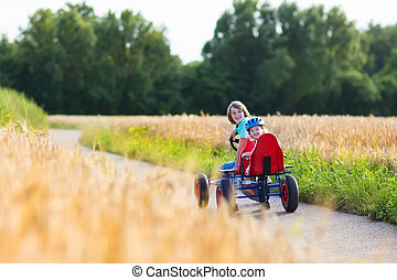 Kids having fun with a go cart car - Two happy children,...