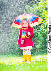 Little girl playing in the rain - Funny cute curly toddler...