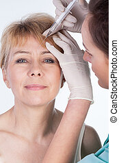 Botox injected in a forehead - Close-up of botox injected in...
