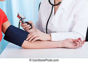 Doctor doing professional pressure examine her young patient
