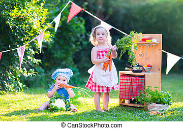 Little kids playing with toy kitchen in the garden - Funny...
