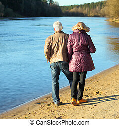 Elderly couple walking hand in hand along the shore. View from the back.