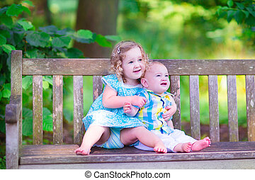 Brother and sister in a park - Adorable kids, little curly...
