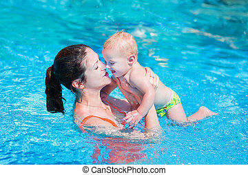Mother and baby in swimming pool - Happy young mother and...