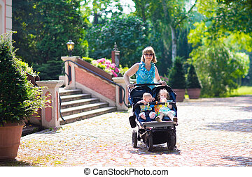 Woman with a double stroller - Young beautiful woman in a...