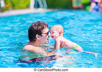 Father and baby in a swimming pool - Young active father...