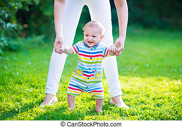 Baby talking his first steps - Cute funny happy baby in a...