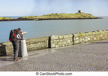 man looking to Dalkey island by binoculars - Young man using...