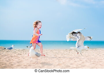 Little girl playing with seagulls - Funny lauging toddler,...