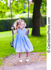 Little girl on a swing - Happy laughing toddler girl with...