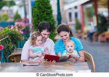 Family at an outside cafe - Happy family of four, young...