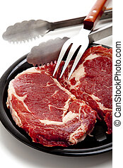 Red Meat - A group of raw beef ribeye steaks on a white...