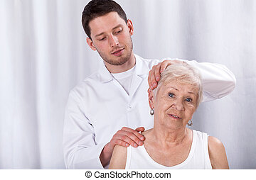 Physiotherapist helping patient with neck ache -...