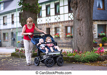 Woman with double stroller - Young beautiful woman with a...