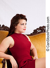 Woman sitting on gold couch