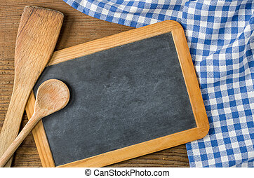 Chalkboard with wooden spoons on a blue checkered tablecloth