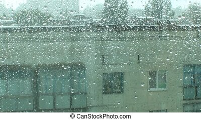 its raining behind the window in the city