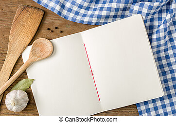 Book with wooden spoons on a blue checkered tablecloth