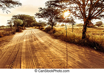 Empty road going through rural landscape under sunset sky