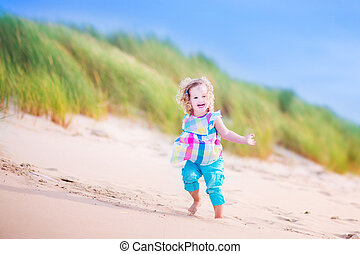 Little girl runnign in sand dunes