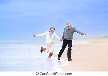 Middle aged couple running on a beach - Happy middle aged...