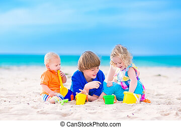 Three kids playing on a beach - Three kids, teen age boy,...