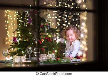 Little girl at Christmas dinner - Cute curly toddler girl...