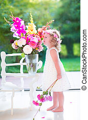 Little girl smelling flowers at home - Beautiful little girl...