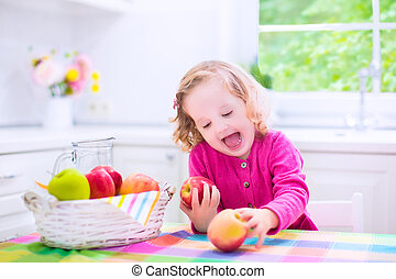 Little girl eating apples - Funny happy laughing child,...