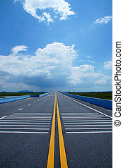 Empty road and the yellow traffic lines with clouds