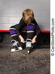 Boy Tying Hockey Skates in Dressing Room - A Young Boy Ties...