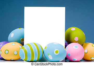Brightly colored Easter Eggs surrounding white, blank...