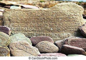 Mani wall and stones with buddhist symbols