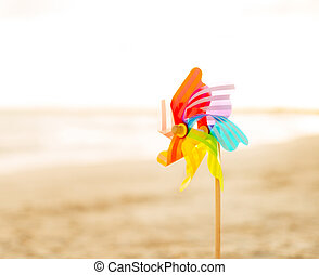 Closeup on colorful windmill toy standing on the beach in...