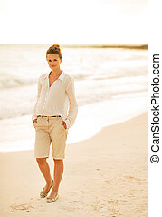 Full length portrait of young woman walking on the beach in the