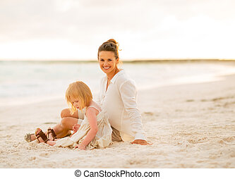 Happy mother and baby girl sitting on the beach in the evening