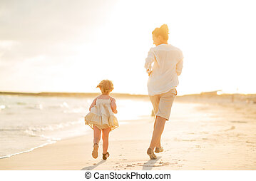 Mother and baby girl running on the beach in the evening...