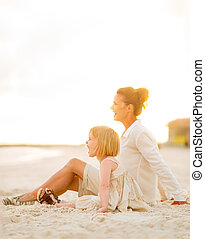Happy baby girl and mother sitting on the beach in the evening a
