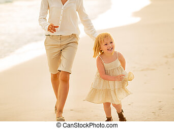 Mother and baby girl running on the beach in the evening