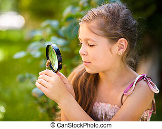 Young girl is looking at flower through magnifier, outdoor...