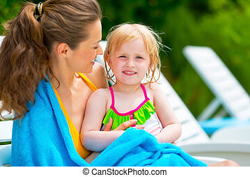 Portrait of happy baby girl with mother sitting on sunbed