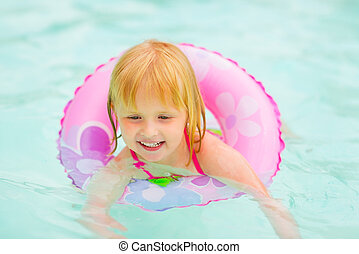 Portrait of baby girl with swim ring swimming in pool